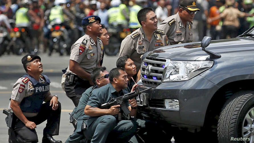 Police officers react near the site of a blast in Jakarta, Indonesia, January 14, 2016. Several explosions went off and gunfire broke out in the centre of the Indonesian capital on Thursday and police said they suspected a suicide bomber was responsi