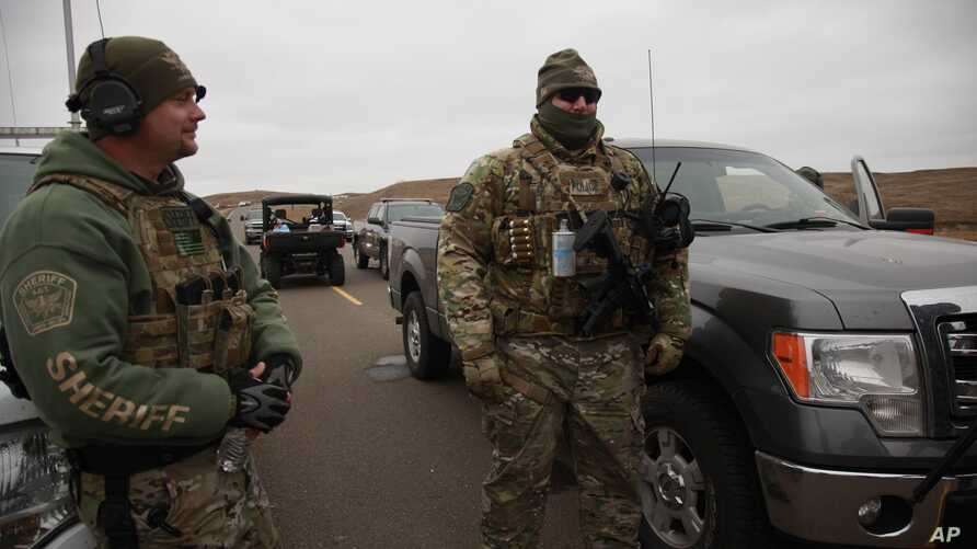 Two members of a local SWAT team talk as they watch protesters demonstrating against the Dakota Access Pipeline encroaching a water source near the Stand Rock Sioux Reservation, in Cannon Ball, North Dakota, Oct. 30, 2016.