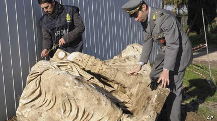 Guardia di Finanza police officers inspect a statue believed to be that of Roman emperor Caligula in Nemi, north of Rome in this January 2011 handout photo.