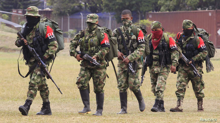 FILE - Defected members of Colombian guerrilla group ELN walk to a military base to surrender and handover their weapons, July 16, 2013.