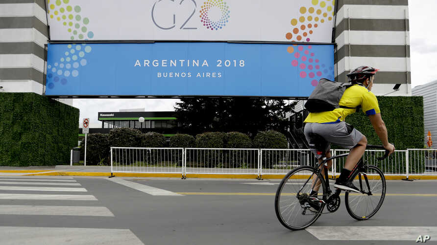 A man rides a bicycle past a banner promoting the G20 summit at the Costa Salguero Center, in Buenos Aires, Argentina, Nov. 27, 2018.