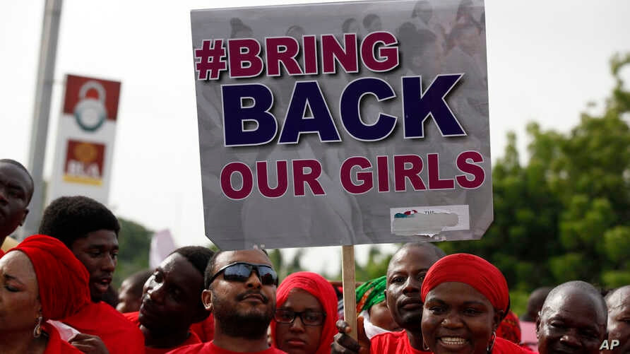 FILE - Nigerians carry a sign calling on the government to rescue the kidnapped girls during a demontration in Abuja.