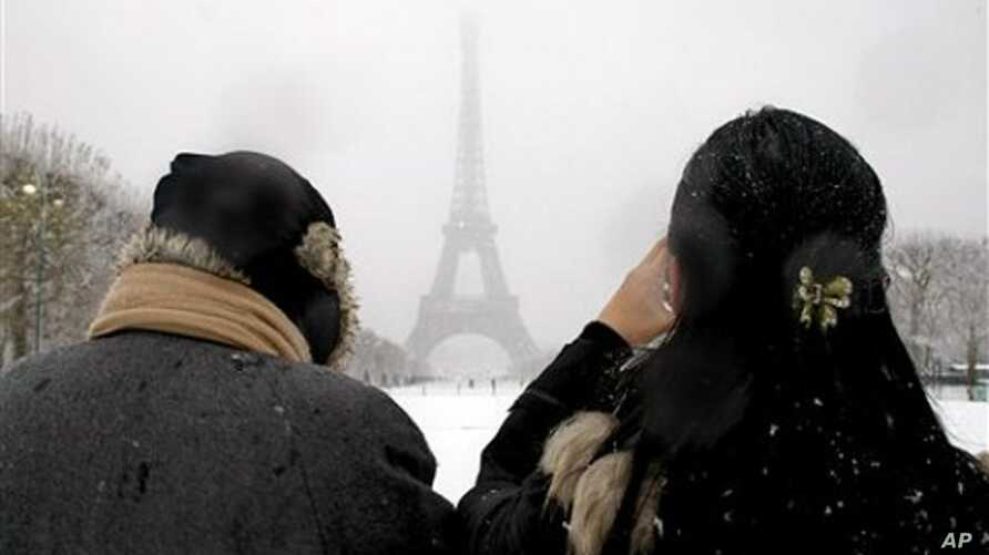 People take snapshots near the Eiffel Tower after snow fell on the French capital, 8 Dec. 2010