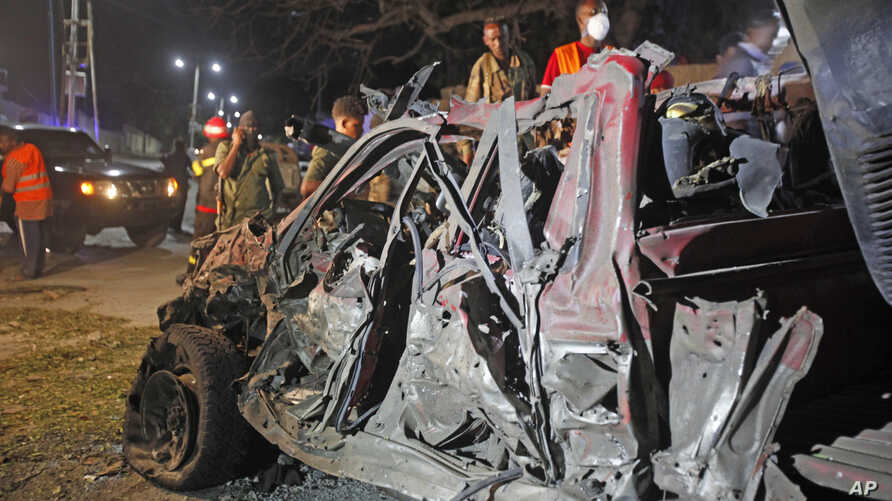 Soldiers stand near the wreckage of a suicide car bomb outside Somalia's presidential palace, Sept, 21, 2015.
