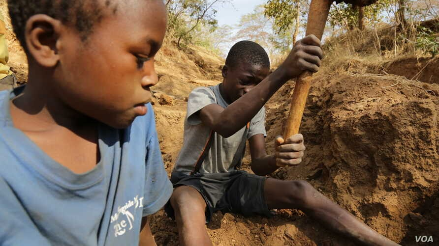 FILE - Two 13-year-old boys dig for gold ore at a small-scale mine in Mbeya Region, Tanzania, in this 2013 photo.