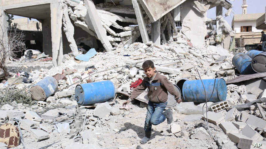 FILE - A boy runs over rubble at a site hit by what activists say were airstrikes by forces loyal to Syria's President Bashar al-Assad in the rebel-controlled area of Deir al-Asafir town, near Damascus, March 11, 2015.