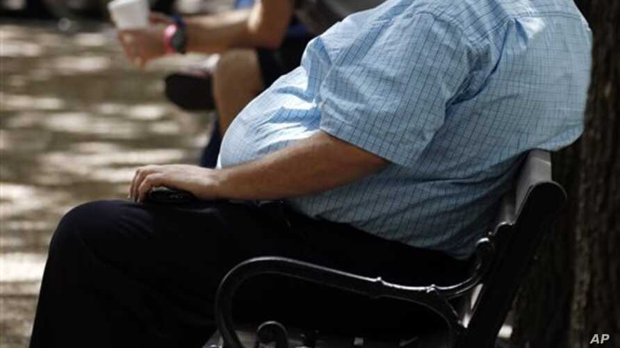 In this Sept. 4, 2014, file photo, an overweight man rests on a bench in Jackson, Miss. Rising numbers of American adults have the most dangerous kind of obesity, belly fat, despite evidence that overall obesity rates may have plateaued, government