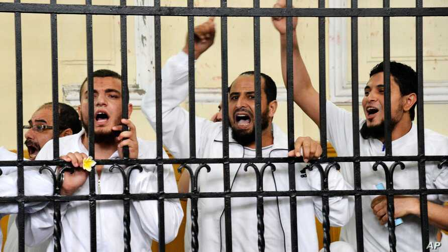 Supporters of the Muslim Brotherhood and other Islamists call out from the defendants cage as they receive sentences ranging from death by hanging for one, life in prison for 13 and 8-15 years for the others after they were convicted of murder, rioti