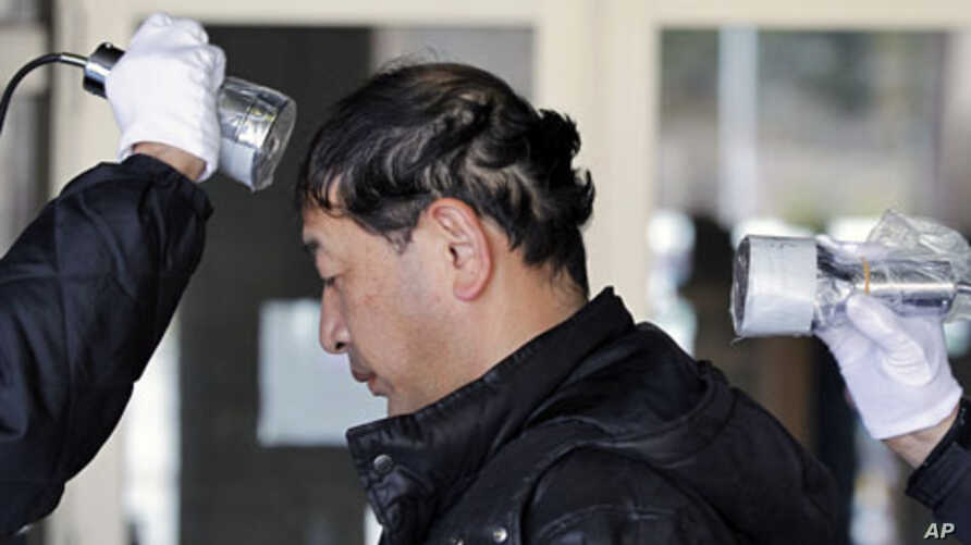 Shyudou Kaneyama is tested for possible nuclear radiation at an evacuation center in Fukushima, north of Japan. Kaneyama was evacuated from his home in Namie, located about 16 km from the crippled nuclear plant. March 28, 2011