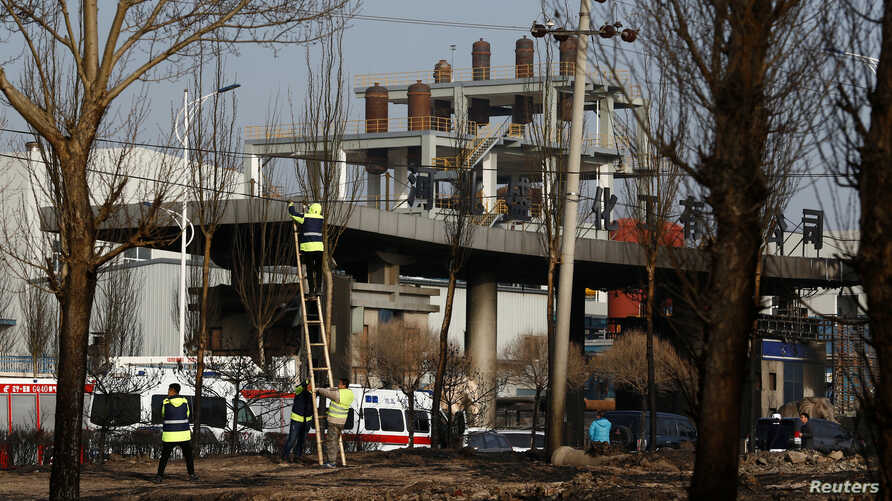 Workers fix a wire at the site of a blast outside a chemical plant in Zhangjiakou, Hebei province, China, Nov. 28, 2018.