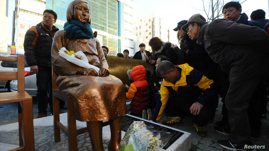 A flower is laid on a statue of a girl that represents the sexual victims by the Japanese military during a rally in front of Japanese Consulate in Busan, South Korea, Dec. 30, 2016.