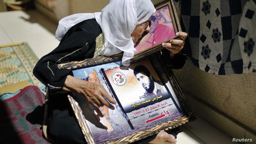 A mother of a Palestinian who has been held prisoner by Israel for 22 years, kisses his picture in Gaza City in this July 28, 2013, file photo.