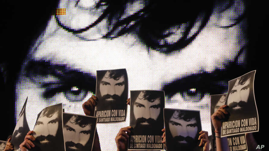 Demonstrators hold photos of missing activist Santiago Maldonado, during a protest at Plaza de Mayo in Buenos Aires, Argentina, Sept. 1, 2017. Human rights groups say Maldonado went missing a month ago, after Argentine border police captured him duri