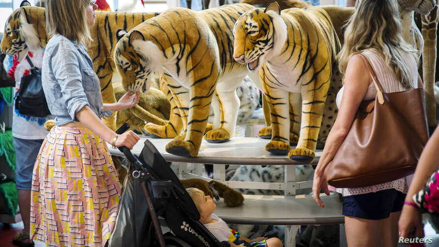 Customers look at large stuffed tigers inside of a toy store in New York, July 15, 2015. A new study suggests that regularly seeing certain endangered animals depicted as cartoons or toys can give the public a false perception that the animal's popul