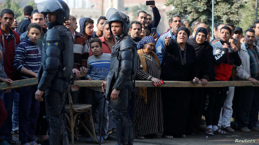 People gather at the site of attack on a church in the Helwan district south of Cairo, Egypt, Dec. 29, 2017.