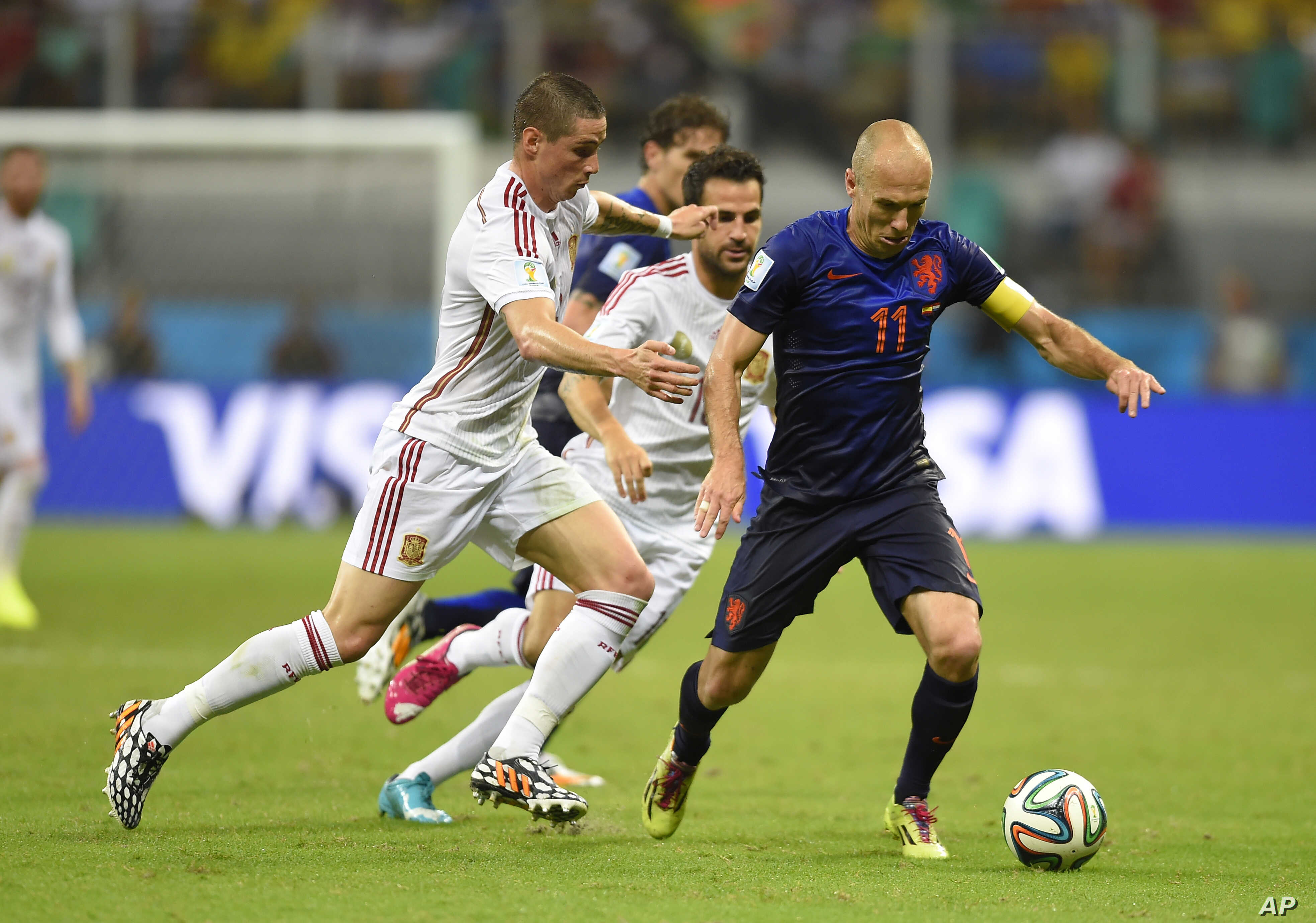 Netherlands' Arjen Robben, right, is challenged by Spain's Fernando Torres during the World Cup match between Spain and the Netherlands, Friday, June 13, 2014.