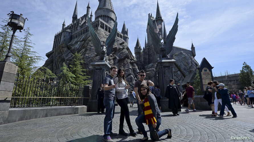 "Guests pose before they enter Hogwarts School during a soft opening and media tour of ""The Wizarding World of Harry Potter"" theme park at the Universal Studios Hollywood in Los Angeles, California March 22, 2016."