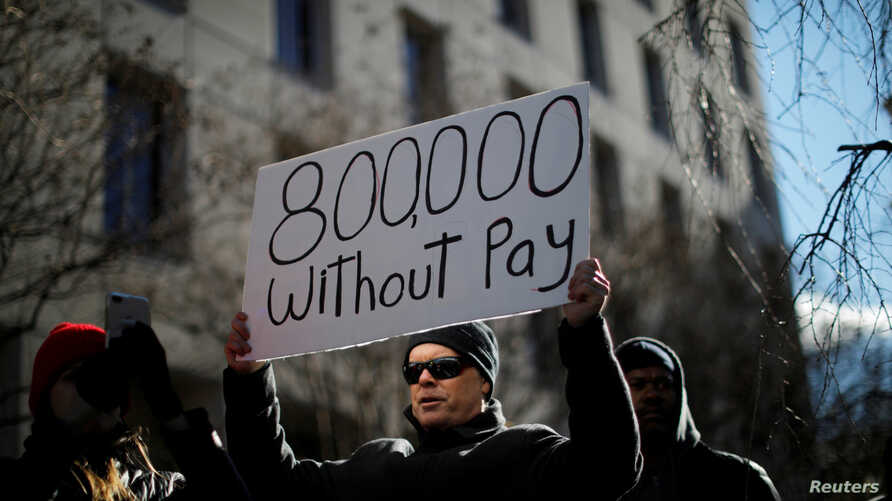 "FILE - A demonstrator holds a sign, signifying hundreds of thousands of federal employees who won't be receiving their paychecks as a result of the partial government shutdown, during a ""Rally to End the Shutdown"" in Washington, Jan. 10, 2019."