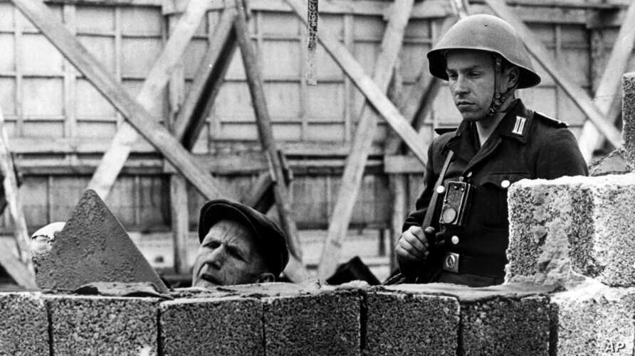This undated 1962 file photo shows an East German People's Republic Army soldier observing a worker as he erects the Berlin Wall near Bernauer Street in Berlin, Germany.