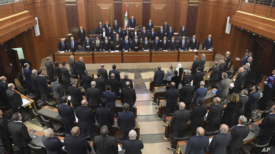 Photo released by the Lebanese Parliament media office, shows new cabinet members, background, and Lebanese lawmakers, foreground standing before a debate for a vote of confidence, in the Lebanese parliament, in Beirut, Feb. 12, 2019.