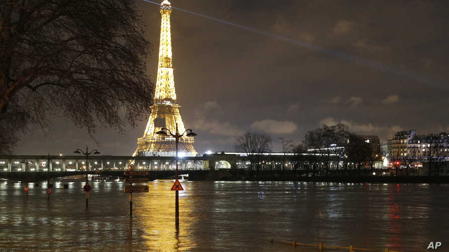 A flooded street lamp and signboards are pictured next to the river Seine in Parison the river Seine in Paris, Jan. 27, 2018.