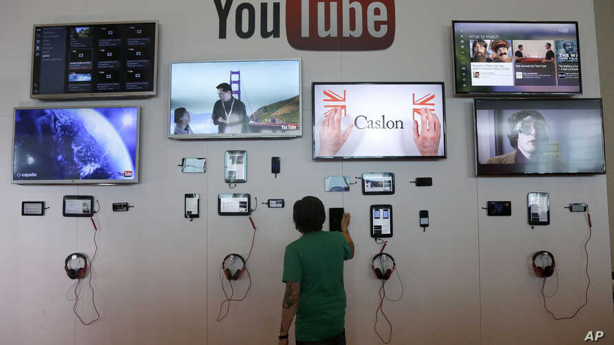 FILE - A man looks at a device a the YouTube booth at Google I/O 2013 in San Francisco.
