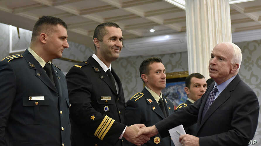 U.S. Sen. John McCain (right) shakes hand with Montenegrin army officers in Podgorica, Montenegro, April 12, 2017. McCain has congratulated Montenegro for its upcoming NATO membership, blasting Russia for its attempts to interfere in the Balkans.