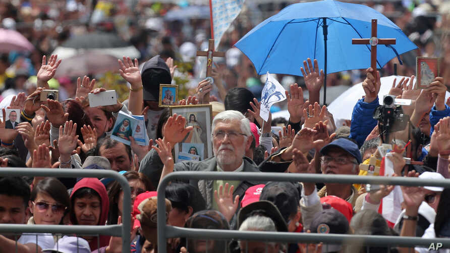 People raise their hands as Pope Francis blesses them after Mass at Bicentennial Park in Quito, Ecuador, July 7, 2015.