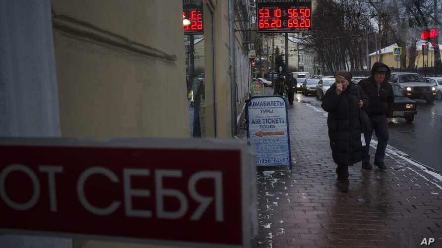 People walk along the Boulevard Ring in downtown Moscow, Russia, Wednesday, Dec. 24, 2014 with a currency exchange office sign on a wall.