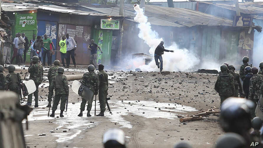 A supporter of opposition leader Raila Odinga throws a canister of tear gas towards riot police during running battles with police in Kibera Slums in Nairobi, Kenya, Nov. 19, 2017.