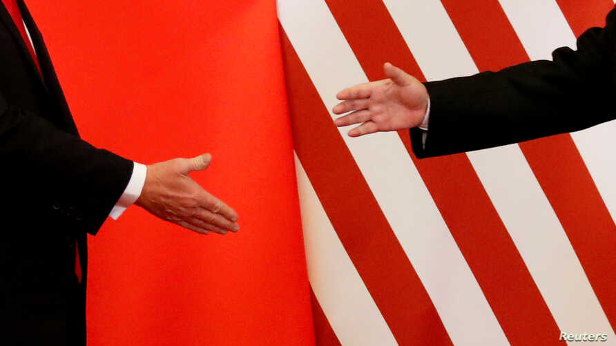 FILE - U.S. President Donald Trump and China's President Xi Jinping shake hands after making joint statements at the Great Hall of the People in Beijing, China, Nov. 9, 2017.