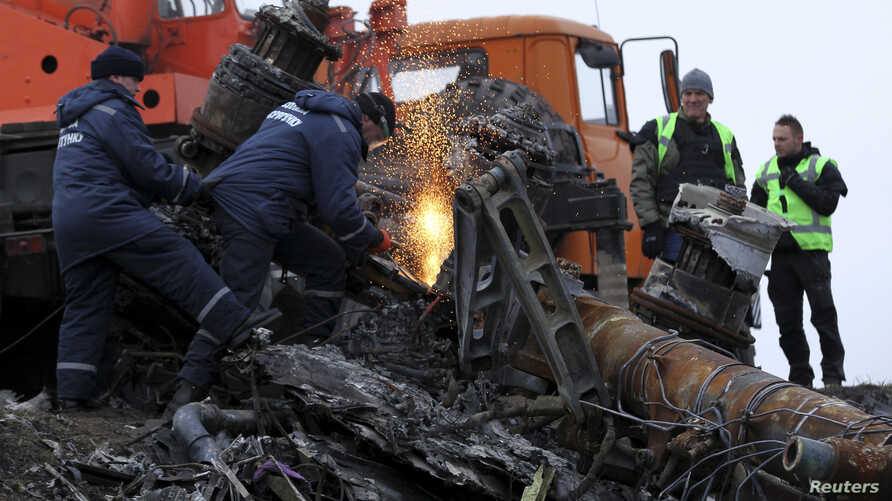 Local workers cut wreckage of the Malaysia Airlines Flight MH17 at the site of the plane crash near the settlement of Grabovo in the Donetsk region, Nov. 16, 2014.