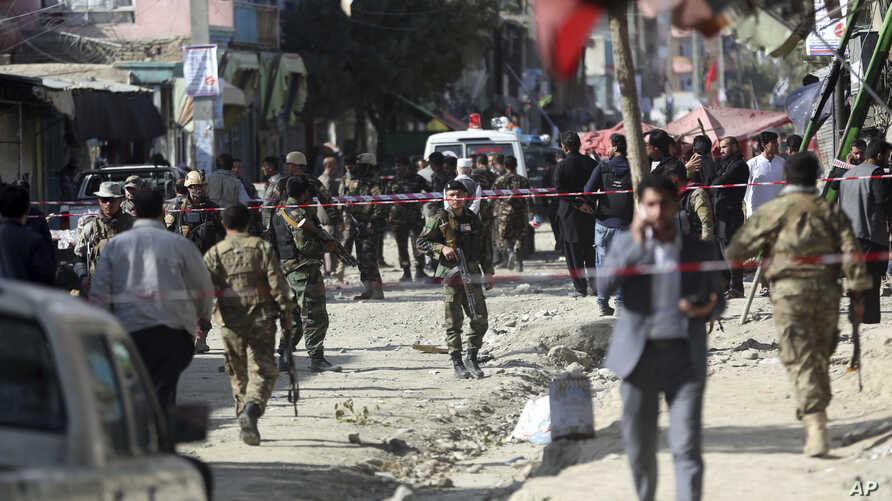 Security forces inspect the site of a suicide attack outside a Shiite mosque in Kabul, Afghanistan, Sept. 29, 2017.