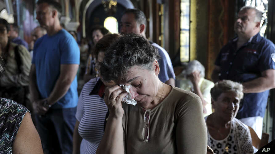 Orthodox faithful attend a memorial service for the victims of a forest fire, inside a church at Mati village, east of Athens, July 29, 2018.