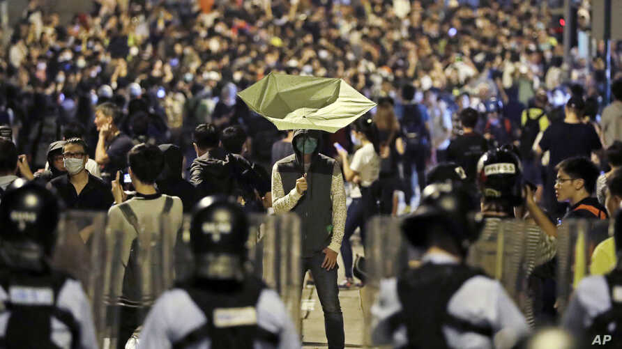 A protester holds a yellow umbrella in front of police officers after clashing as thousands of people march in a Hong Kong street, Nov. 6, 2016.