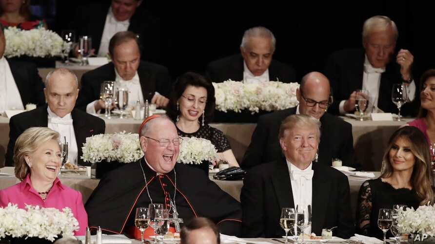 Cardinal Timothy Dolan, second from left, Democratic presidential candidate Hillary Clinton, left, Republican presidential candidate Donald Trump, second from right, and Melania Trump, laugh after a joke during the 71st Annual Alfred E. Smith Memoria