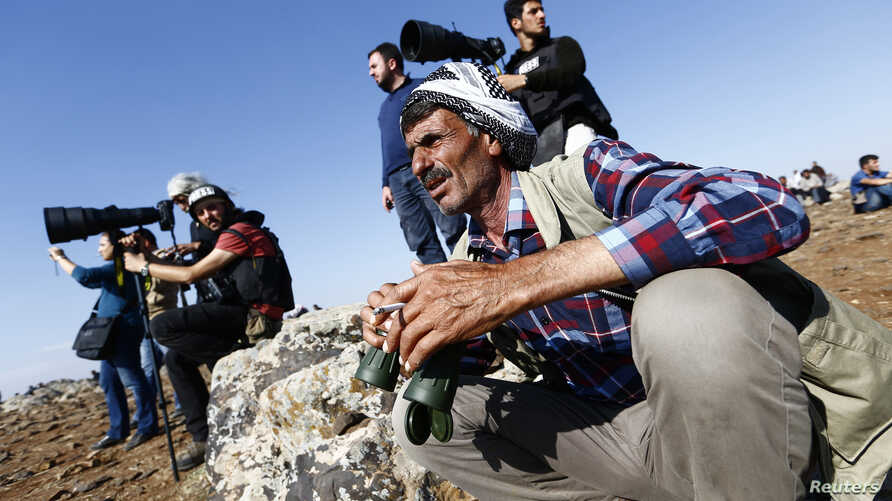 Turkish Kurds watch the Syrian town of Kobani from a hill near the Mursitpinar border crossing, in Suruc, Oct. 24, 2014.