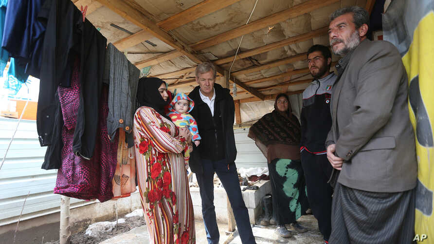 Jan Egeland, secretary-general of the Norwegian Refugee Council, listens to a Syrian family at a refugee camp in Marej, Lebanon; he said in an Associated Press interview that U.N. Security Council resolutions seeking to boost humanitarian access to S