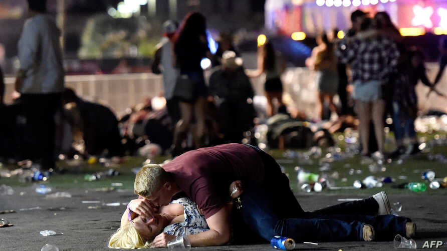 A man lays on top of a woman as others flee the Route 91 Harvest country music festival grounds after a active shooter was reported on Oct. 1, 2017 in Las Vegas, Nevada.