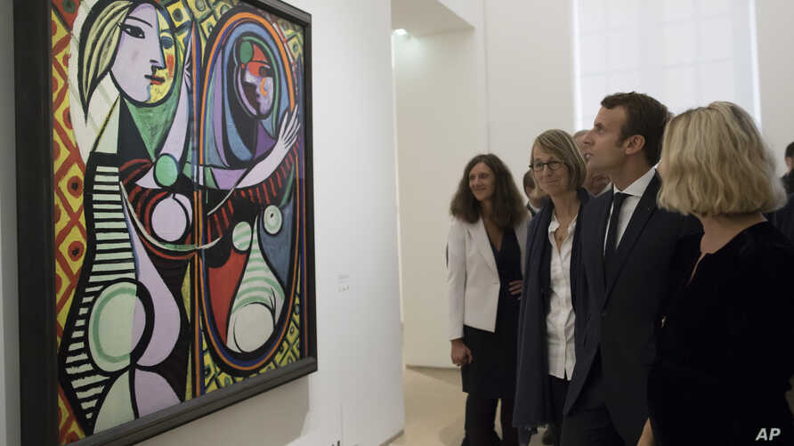 "FILE - France's President Emmanuel Macron visits the ""Picasso 1932: Erotic Year"" exhibition at the Picasso museum in Paris, Sunday, Oct. 8, 2017."