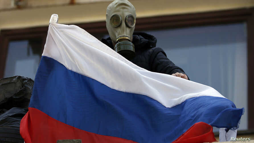 A pro-Russia rebel wearing a gas mask places a Russian flag on the balcony of the city hall in Mariupol, eastern Ukraine May 7, 2014. Ukrainian forces seized the rebel-held city hall in the eastern port city of Mariupol overnight, driving out pro-Rus