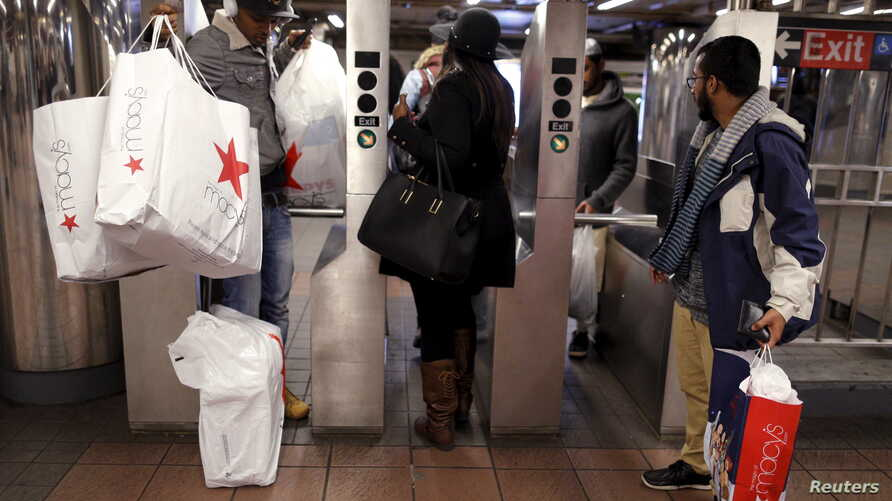 Shoppers enter the Herald Square Subway station after early morning Black Friday Shopping in New York, Nov. 27, 2015.