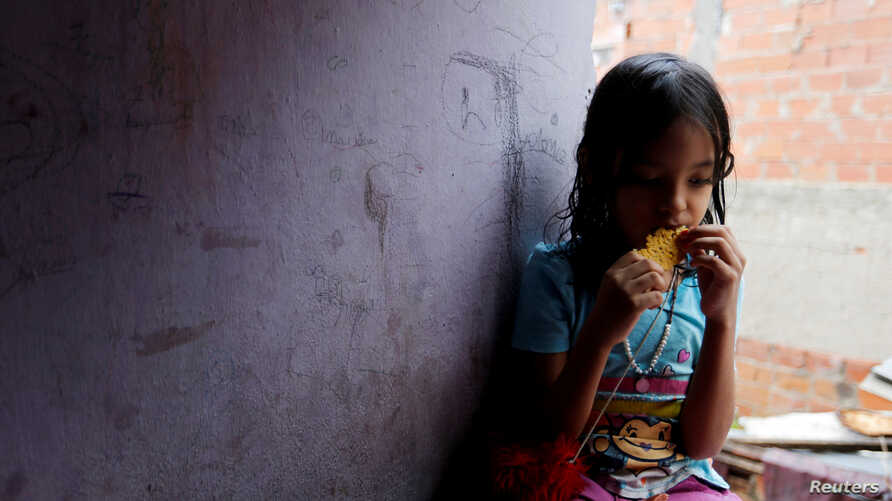One of Yennifer Padron and Victor Cordova's daughters eats an arepa in the family room of the house that they share at Petare slum in Caracas, Venezuela, Aug. 21, 2017.