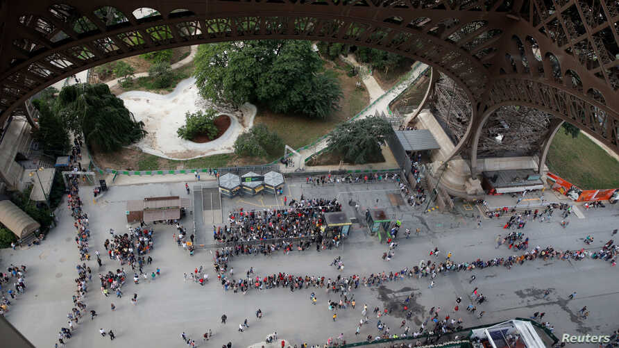 FILE - Visitors queue to visit the Eiffel Tower in Paris, France, June 2, 2018.