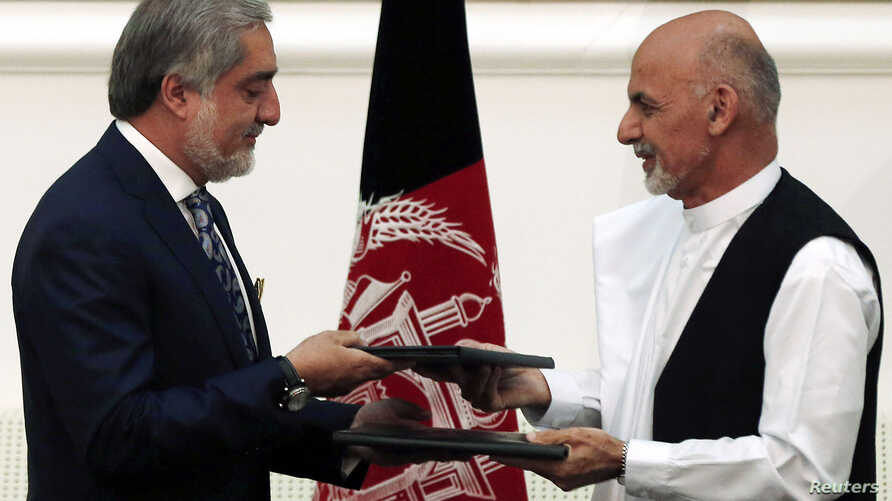 Afghan rival presidential candidates Ashraf Ghani (R) and Abdullah Abdullah and exchange signed agreements for the country's unity government in Kabul Sept. 21, 2014.