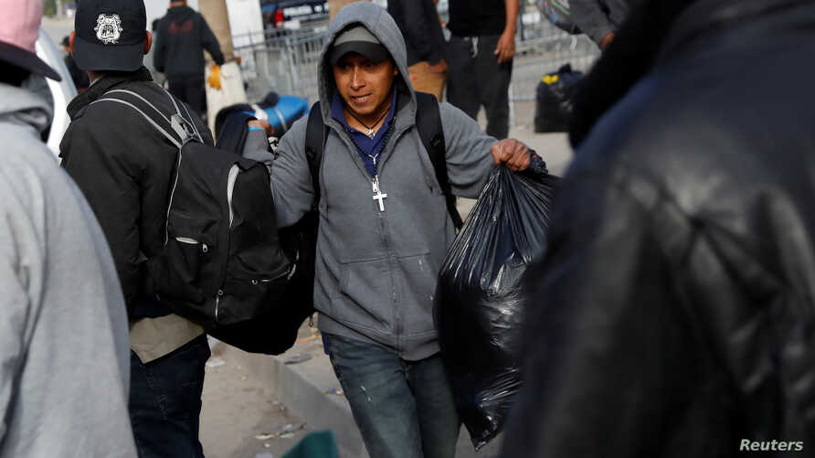A migrant man, part of a caravan of thousands from Central America tying to reach the United States, carries his  belongings in Tijuana, Mexico, Jan. 29, 2019.