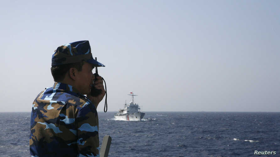 FILE - An officer of the Vietnamese coast guard officer speaks on a radio as he monitors a Chinese vessel (top) in the South China Sea, about 210 km (130 miles) off Vietnam's shore May 15, 2014.