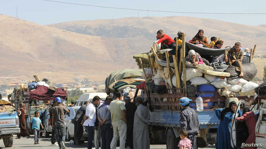 Syrian refugees, fleeing the recent fighting in Arsal, wait by trucks in Majdel Anjar in the Bekaa valley, near the Lebanese border with Syria, Aug. 8, 2014.