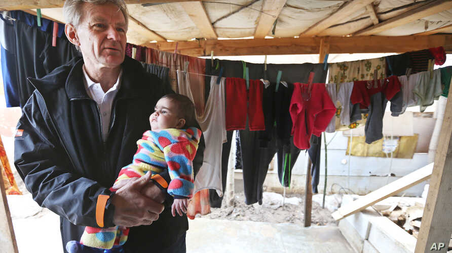 MFILE - U.N. special adviser Jan Egeland holds a Syrian baby during his visit to a refugee camp in the town of Marej in the Bekaa valley, east Lebanon, Feb. 25, 2015.
