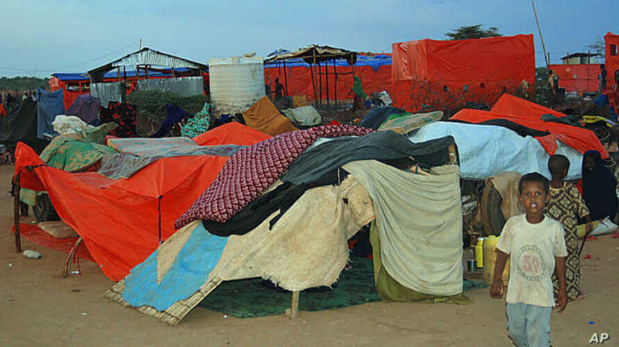 A boy walks by a makeshift shelter for new arrivals at the Dollo Ado refugee transit center in Ethiopia, October 26, 2011 (VOA - P. Heinlein).